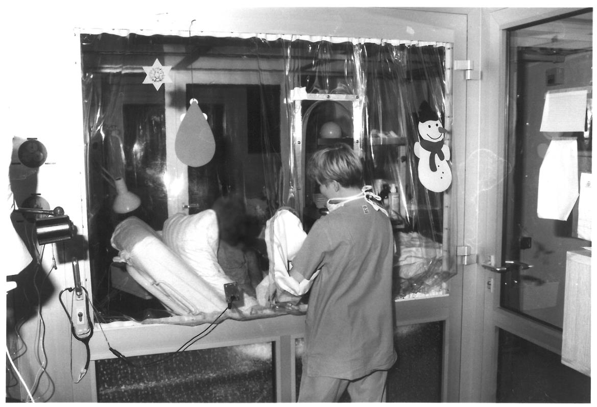 Historical photograph: A nurse stands at the bedside in the bone marrow transplantation ward.