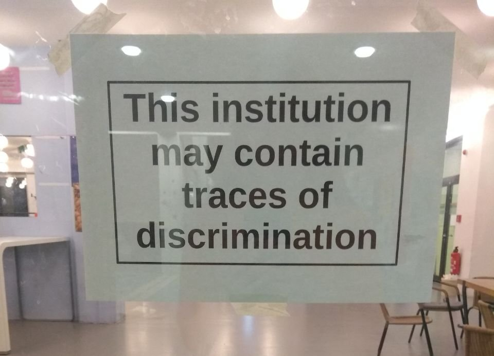 Foto von Zettel hinter Glastür: This institution may contain traces of discrimination